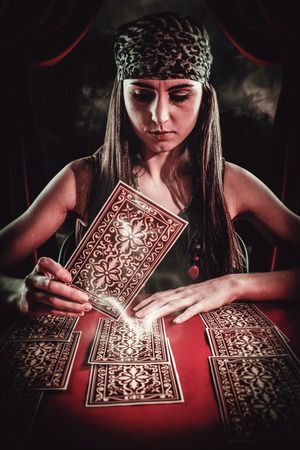 telepathy cards: Fortune teller using tarot cards against gloomy sky