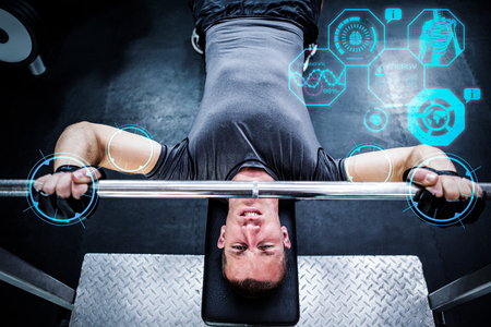 working out: Man working out in gym against fitness interface Stock Photo