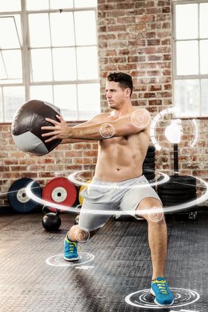 Muskulöser Mann mit Medizinball Ausübung gegen Fitness-Schnittstelle