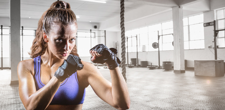 fighting stance: Portrait of female confident boxer with fighting stance against exercise ropes hanging and equipment