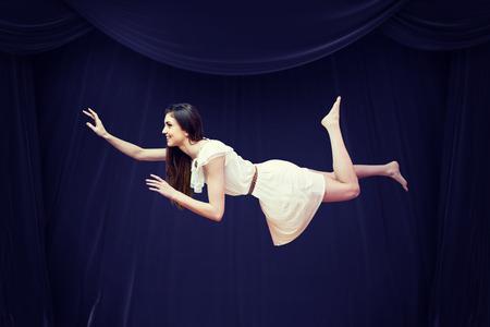 Chica en vestido blanco flotando en el aire contra la cortina roja