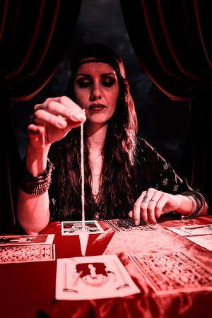 pendulum: Female fortune teller looking at pendulum  against gloomy sky