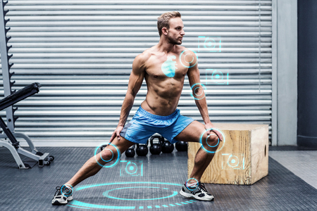 Muscular man doing leg stretchings against fitness interface Stock Photo
