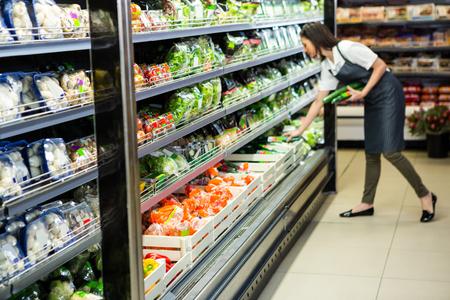 Portré, mosolygós munkás vesz zöldségeket szupermarketben