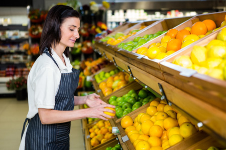 grocery store: Portrait of a smiling worker taking a fruits in supermarket