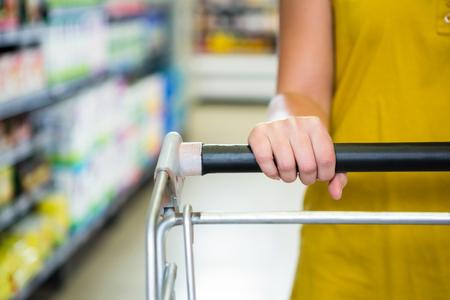 empujando: Detalle de la mujer empuja carrito de supermercado en