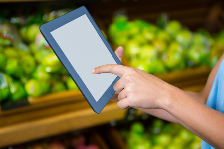woman's hand: Womans hand using tablet in grocery shop
