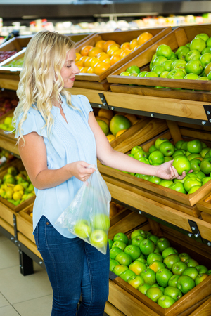 plastic bag: Smiling woman putting apples in plastic bag in grocery shop Stock Photo