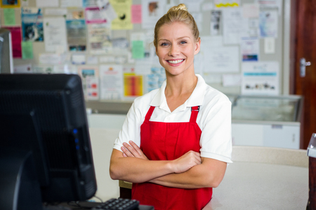 Portrait of smiling shop assistant with arms crossed