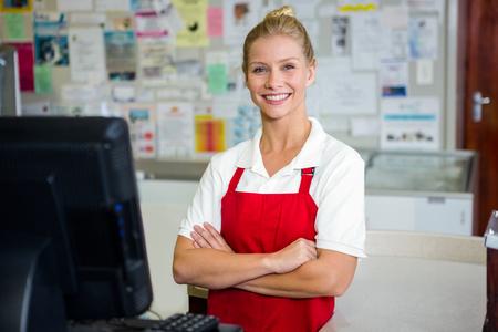 Ritratto di sorridere assistente di negozio con le braccia incrociate Archivio Fotografico