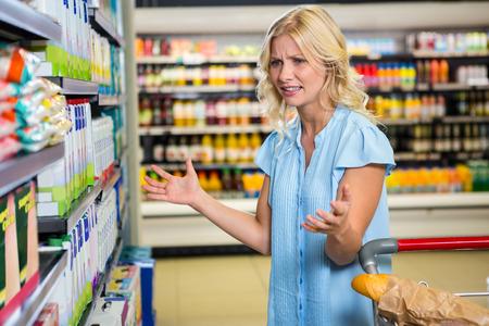 혼란스러운 여자는 슈퍼마켓에서 무엇을 사야할지 몰라요.