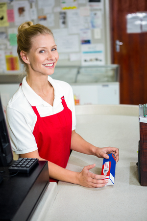 shop assistant: Smiling shop assistant looking at product at supermarket