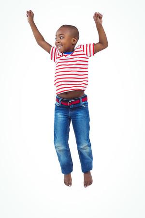 niño saltando: El muchacho sonriente que salta en la pantalla blanca