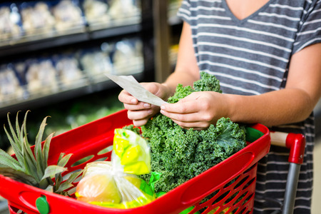 Nő, piros kosár tartja listája szupermarketben
