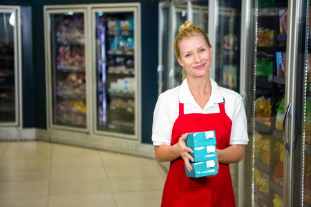 Smiling shop assistant holding products at supermarket