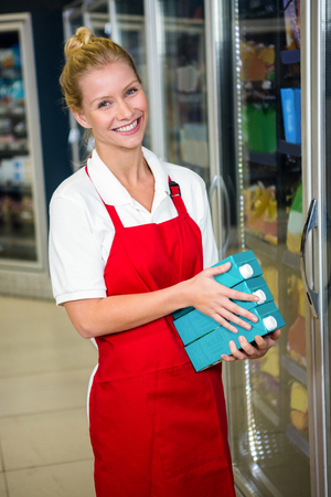 shop assistant: Smiling shop assistant holding products at supermarket Stock Photo