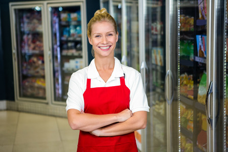 shop assistant: Smiling shop assistant with arms crossed in supermarket