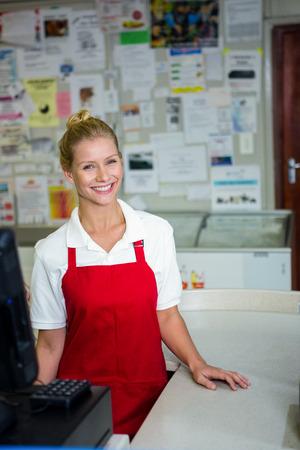 shop assistant: Portrait of smiling shop assistant with red apron