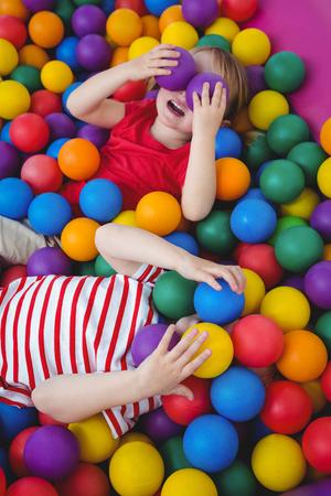 amabilidad: niños sonrientes lindos en piscina de bolas de esponja que cubre los ojos con las bolas