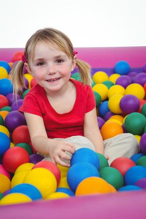 messing: Cute smiling girl in sponge ball pool looking at camera