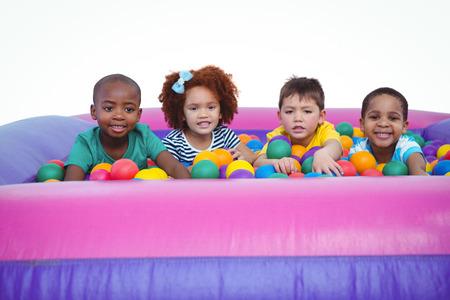 bola de billar: Ni�os sonrientes lindos en piscina de bolas de esponja mirando a la c�mara Foto de archivo