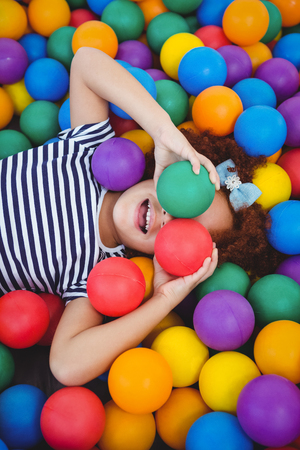 covering eyes: Cute smiling girl in sponge ball pool covering eyes with balls