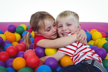 trato amable: ni�os sonrientes lindos en piscina de bolas de esponja que abrazan y que miran la c�mara Foto de archivo