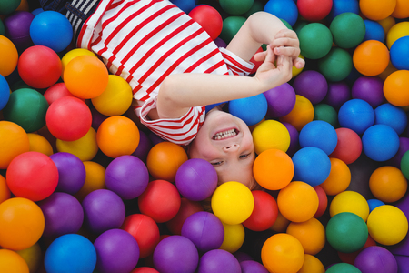 messing: Cute smiling boy in sponge ball pool looking at camera Stock Photo