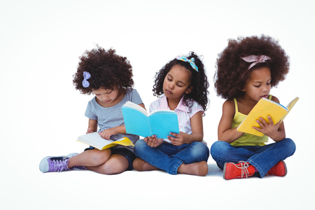 fond of children: Cute girls sitting on the floor reading books on white screen Stock Photo