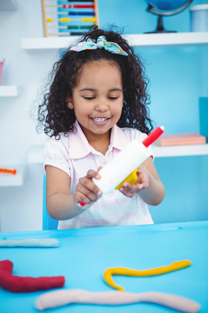 modeling clay: Cute girl using modeling clay in playing room