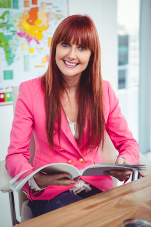 at her desk: Portrait of a hipster businesswoman at her desk in office Stock Photo