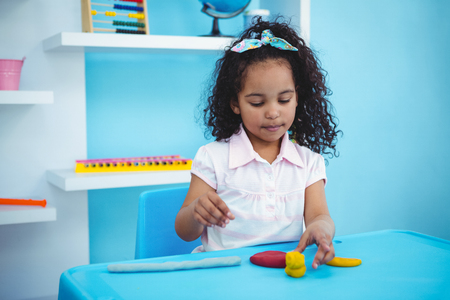 clay modeling: Cute girl using modeling clay in playing room