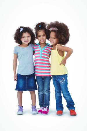 trato amable: Muchachas lindas que abrazan y que miran la c�mara en la pantalla blanca Foto de archivo