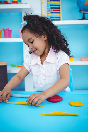 modeling clay: Cute girl playing with modeling clay in playing room Stock Photo