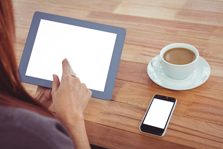 over the shoulder: Over shoulder view of hipster woman using tablet at desk