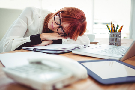 sleeping on desk: Hipster businesswoman falling in sleep at her desk in office