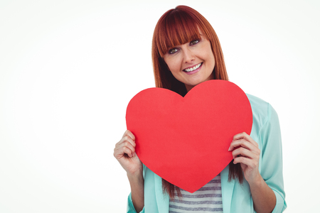 big behind: Smiling hipster woman behind a big red heart against white background