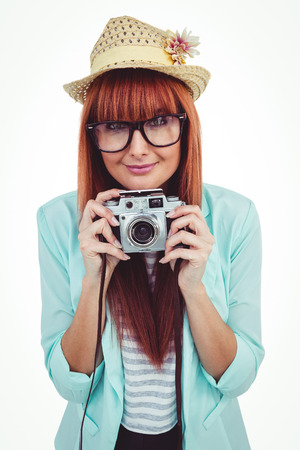 beautiful bangs: Portrait of a smiling hipster woman holding retro camera against white background