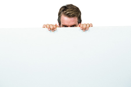 Close-up portrait of man hiding behind board against white background
