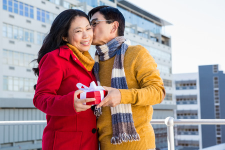 stylish couple: Older asian couple on balcony with gift on a cold day