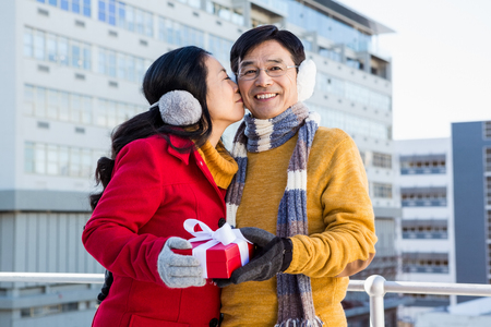 ear muff: Older asian couple on balcony with gift on a cold day