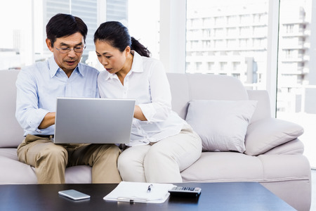 figuring: Smiling man at home on couch using laptop with woman Stock Photo