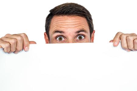 blank sheet: Hombre que sostiene la hoja en blanco en la pantalla blanca Foto de archivo
