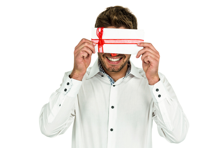 covering eyes: Handsome man covering eyes with gift box on white screen Stock Photo
