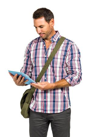 shoulder bag: Smiling man with shoulder bag using tablet on white screen Stock Photo