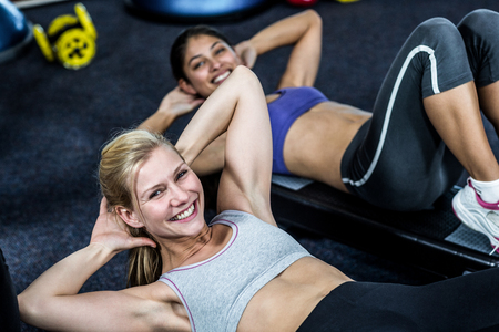 Pretty women working their abs in gym Stock Photo