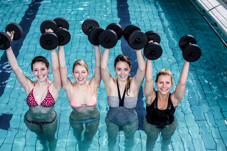 aerobics class: Fit people doing an aqua aerobics class in swimming pool