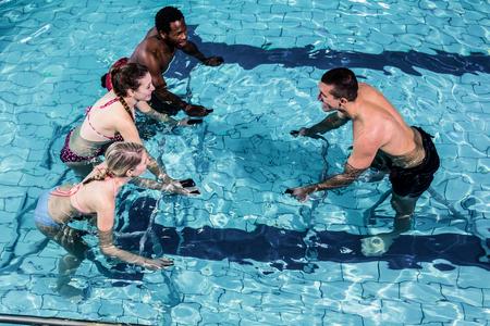 gimnasia aerobica: Clase de la aptitud que hace aeróbicos aqua en bicicletas de ejercicio en la piscina