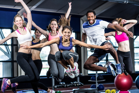 Fit group smiling and jumping in gym Stockfoto