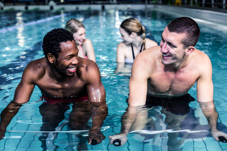 pedaling: Fit smiling group pedaling on swimming bike in pool Stock Photo
